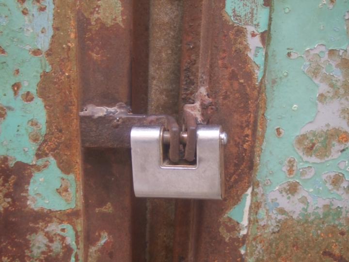 Una puerta cerrada con candando evita observar el interior de las ruinas
