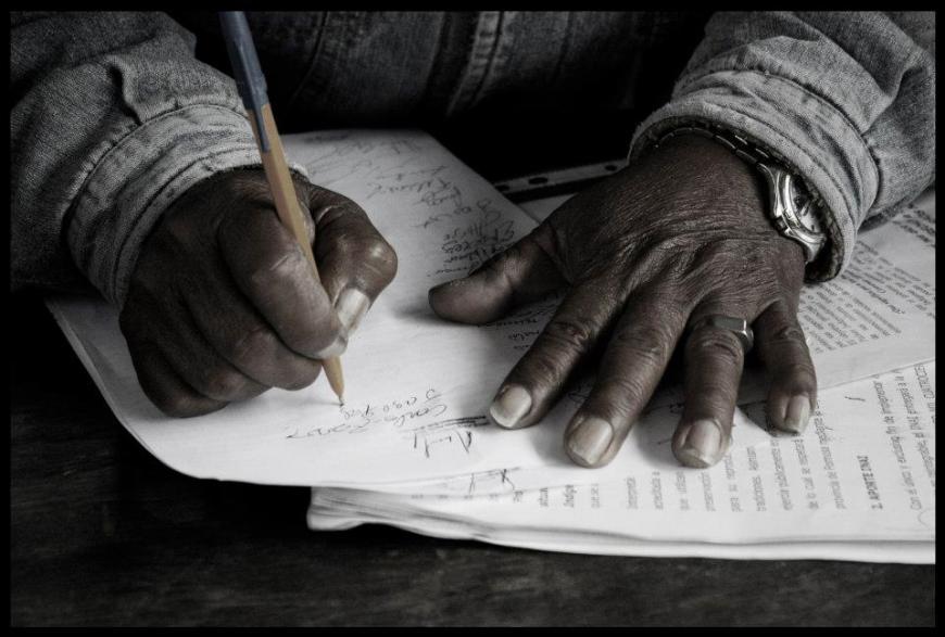 manos firmando asamblea qom